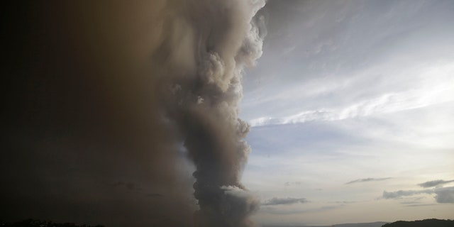 A tiny volcano near the Philippine capital that draws many tourists for its picturesque setting in a lake belched steam, ash and rocks in a huge plume Sunday, prompting thousands of residents to flee and officials to temporarily suspend flights.