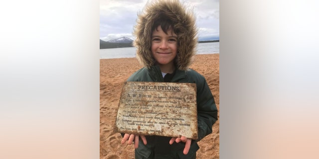 "Seven-year-old Patrick McAlindon with a sign from a crate of incendiary bombs he found on a beach at Loch Morlich in the Scottish Highlands on Christmas Day. After just 15 minutes of scanning the beach at Loch Morlich Patrick was stunned when his new gadget showed an ""off the scale"" reading. (Credit: SWNS)"