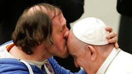 Pope Francis receives kiss on forehead from front-row admirer