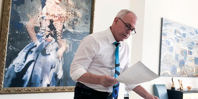 In this Jan. 20, 2020 photo, Robert Julian Stone looks over his medical records in his home in Palm Springs, Calif. Stone, a former University of Michigan student, alleges that the late University of Michigan Athletic Department physician Robert E. Anderson sexually assaulted him during a medical examination in 1971. (Kim Kozlowski/Detroit News via AP)