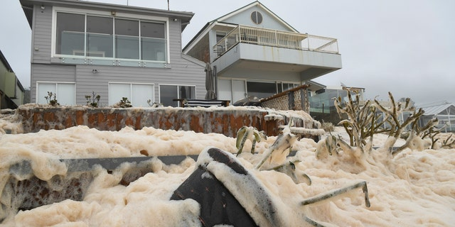 Sea foam brought by waves approaches on beach front houses after heavy rain and storms at Collaroy in Sydney's Northern Beaches, Monday, February 10, 2020.