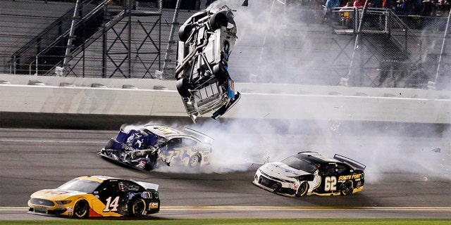 Ryan Newman, top center, goes airborne as he is hit by Corey LaJoie (32) on the final lap of the NASCAR Daytona 500 auto race at Daytona International Speedway, Monday, Feb. 17, 2020, in Daytona Beach, Fla. Sunday's race was postponed because of rain. (AP Photo/Terry Renna)