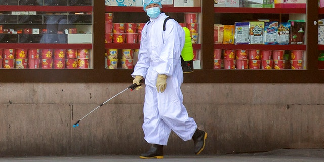 A worker sprays disinfectant outside the Beijing Railway Station in China on Saturday. (AP)