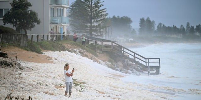 A resident inspects sea foam brought by waves approaching on beach front houses after heavy rain and storms at Collaroy in Sydney's Northern Beaches, Monday, February 10, 2020.