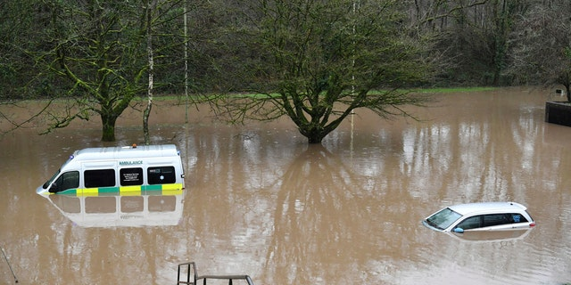 An ambulance, left, and a vehicle are submerged after flooding in Nantgarw, Wales, Sunday, Feb. 16, 2020.