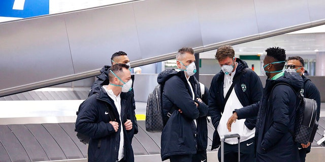 Members of Bulgarian soccer team Ludogorets are seen wearing protective face masks at Malpensa airport in Milan, Italy, ahead of their Europa League soccer match on Feb. 27.