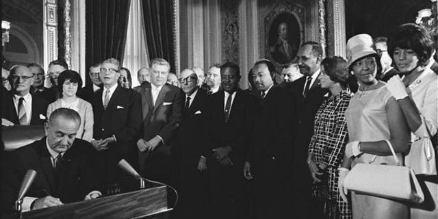 President Lyndon Johnson signing the Voting Rights Act which enforced the 15th Amendment.