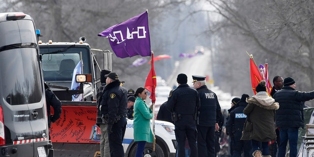 A woman speaks with Ontario Provincial Police officers as she removes flags from a rail blockade in Tyendinaga Mohawk Territory, near Belleville, Ont., on Monday Feb. 24, 2020, during a protest in solidarity with Wet'suwet'en Nation hereditary chiefs attempting to halt construction of a natural gas pipeline on their traditional territories. (Adrian Wyld/The Canadian Press via AP)