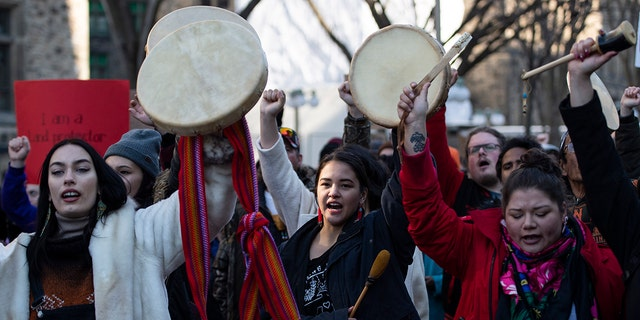 People raise their hands and drums as they rally in solidarity with Wet'suwet'en hereditary chiefs opposed to the Costal GasLink Pipeline, in Ottawa, on Monday, Feb. 24, 2020. (Justin Tang/The Canadian Press via AP)