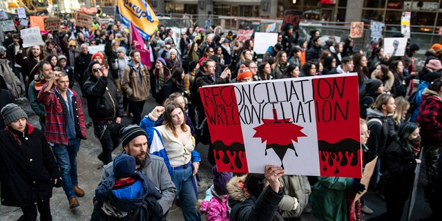 People walk on Kent Street in Ottawa at a rally in solidarity with Wet'suwet'en hereditary chiefs opposed to the Costal GasLink Pipeline, on Monday, Feb. 24, 2020. (Justin Tang/The Canadian Press via AP)