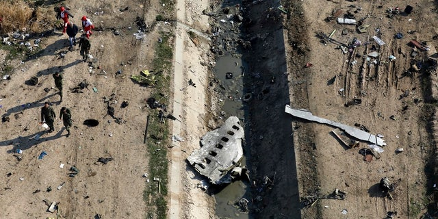 Rescue workers search the scene where a Ukrainian plane crashed in Shahedshahr, southwest of Tehran, Iran on Jan. 8.The downing of a Ukrainian jetliner near Tehran highlights the limits of the civilian arm of Ir an's government against the absolute power of the Shiite theocracy and the paramilitary forces beneath it. (AP Photo/Ebrahim Noroozi, File)