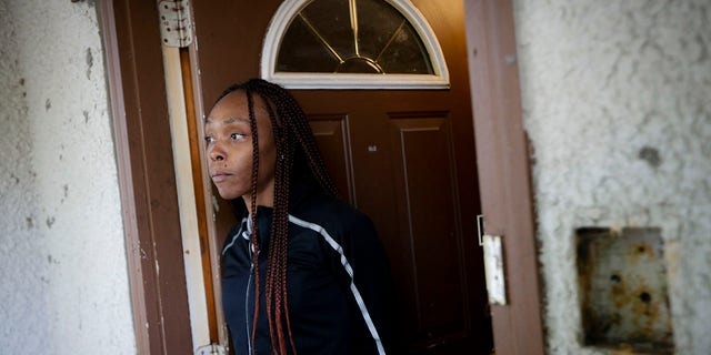 Latosha Evans, a friend of Myon Burrell who says she was with the Burrell the evening Tyesha Edwards was shot and killed at home in 2002, stands in her doorway, Wednesday, Oct. 23, 2019, in Minneapolis. (Associated Press)