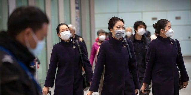 Flight crew members wearing face masks walk through the international arrivals area at Beijing Capital International Airport on Jan. 30. (AP Photo/Mark Schiefelbein)