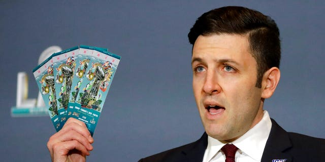 Michael Buchwald, NFL Senior Counsel, holds up authentic tickets for the NFL Super Bowl 54 football game during a news conference about seizures of counterfeit game-related merchandise and tickets, Thursday, Jan. 30, 2020, in Miami Beach, Fla. (AP Photo/Chris Carlson)