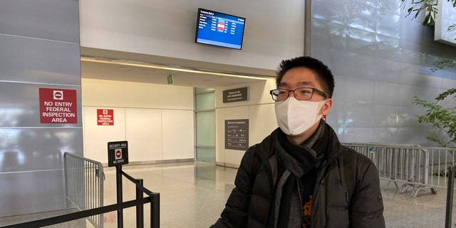 In this Wednesday, Jan. 29 photo, traveler Bill Chen stands outside of customs at San Francisco International Airport after arriving on a flight from Shanghai, where he was conducting business and visiting family over the Lunar New Year holiday. (AP Photo/Terry Chea)