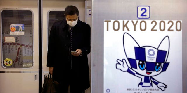 A poster promoting the Tokyo 2020 Olympics is posted next to a train door as a commuter wearing a mask looks at his phone on a train in Tokyo. Tokyo Olympic organizers are trying to shoot down rumors that this summer's games might be canceled or postponed because of the spread of a new virus. (AP Photo/Jae C. Hong)