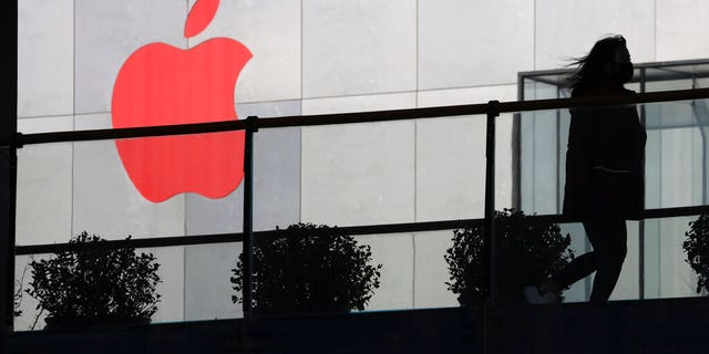 FILE: A woman runs past an Apple logo colored red in Beijing, China.
