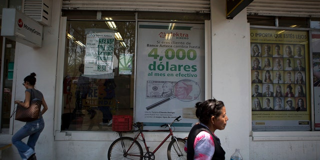 FILE - In this April 5, 2016 file photo, pedestrians walk past signs advertising money transfer services and loans, outside a business in Mexico City. Mexican migrants working abroad sent home a record $36 billion in remittances in 2019, the country's central bank reported Tuesday, Feb. 4, 2020. (AP Photo/Rebecca Blackwell, File)