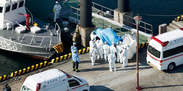 Medical workers in protective suits lead a passenger tested positive for a new coronavirus from the cruise ship Diamond Princess at Yokohama Port in Yokohama, south of Tokyo, Wednesday, Feb. 5, 2020.. (Hiroko Harima/Kyodo News via AP)