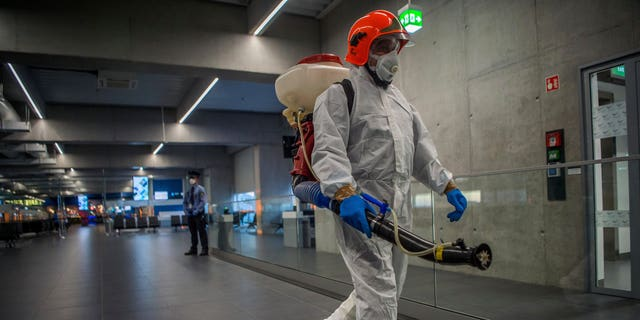 Disinfection equipment is carried by a worker as precautionary measures against the spreading of novel coronavirus, at Budapest Liszt Ferenc International Airport in Budapest, Hungary, Wednesday, Feb. 5, 2020. (Zoltan Balogh/MTI via AP)
