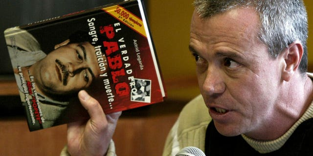 """FILE: Jhon Jairo Velasquez, a former hitman for Pablo Escobar, known by his nickname """"Popeye,"""" gives his testimony while holding a book titled """"The True Pablo, Blood, Treason, and Death,"""" during the trial against Alberto Santofimio Botero in Bogota, Colombia."""