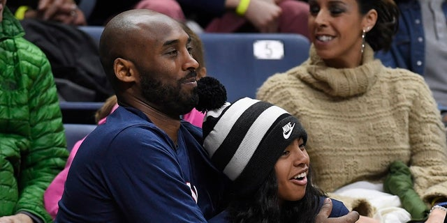 Kobe Bryant and his daughter Gianna watch the first half of an NCAA college basketball game between Connecticut and Houston in Storrs, Conn. (AP Photo/Jessica Hill, File)