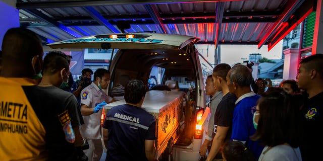 Morgue staff loading a coffin of a shooting victim at a morgue in Korat, Nakhon Ratchasima, Thailand, on Sunday. (AP Photo/Gemunu Amarasinghe)