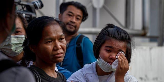 Relatives of the dead waiting outside a morgue Sunday. (AP Photo/Gemunu Amarasinghe)