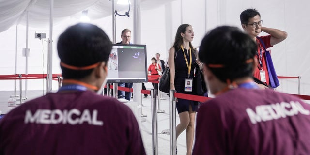 Visitors pass through a thermal scanner as they arrive the Singapore Air Show on Tuesday, Feb. 11, 2020, in Singapore. (AP Photo/Danial Hakim)