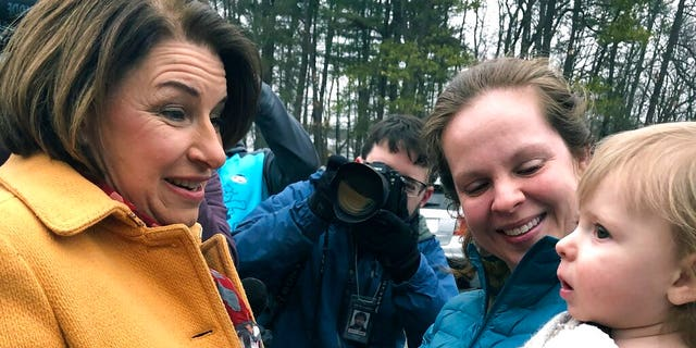 Democratic presidential candidate Sen. Amy Klobuchar, D-Minn., left, greets people outside a New Hampshire primary polling location, Tuesday, Feb. 11, 2020, in Manchester, N.H. (AP Photo/Holly Ramer)