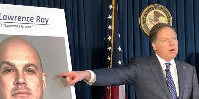 U.S. Attorney Geoffrey Berman points to a photo showing Lawrence Ray during a news conference, Tuesday, Feb. 11, 2020, in New York. Ray, an ex-convict known for his role in a scandal involving former New York police commissioner Bernard Kerik, was charged Tuesday with federal extortion and sex trafficking charges involving a group of students at Sarah Lawrence College.