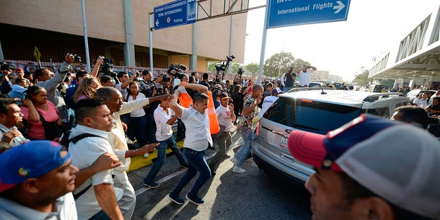 Supporters of Venezuela's President Nicolas Maduro attack a vehicle carrying opposition leader Juan Guaido after he arrived at the Simon Bolivar International Airport in La Guaira, Venezuela, Tuesday, Feb. 11, 2020. Guaido returned home from a tour of nations that back his effort to oust socialist leader Nicolas Maduro. (AP Photo/Matias Delacroix)