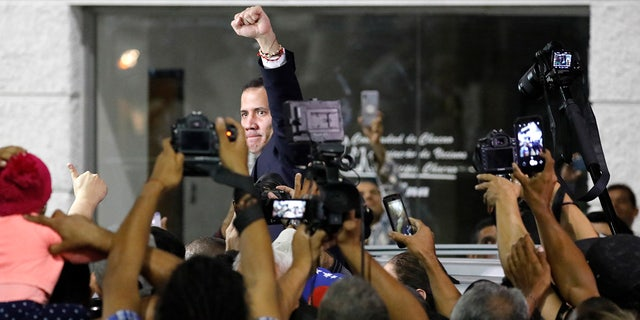 Surrounded by the media, opposition leader Juan Guaido pumps his fist after a rally at Bolivar Plaza in Chacao, Venezuela, Tuesday, Feb. 11, 2020. Guaido returned home from a tour of nations that back his effort to oust socialist leader Nicolas Maduro. (AP Photo/Ariana Cubillos)