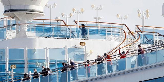 Passengers stand on the deck of the Diamond Princess cruise ship anchored at Yokohama Port. (Yuta Omori/Kyodo News via AP)