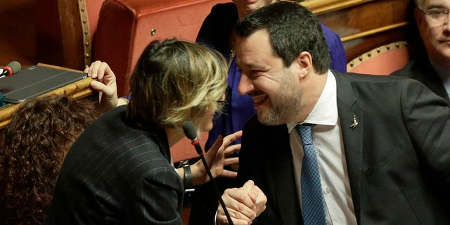 Opposition populist leader Matteo Salvini greets senator Giulia Bongiorno during the debate at the Italian Senate on whether to allow him to be prosecuted – as he demands to be -- for alleging holding migrants hostage for days aboard coast guard ship Gregoretti instead of letting them immediately disembark in Sicily, while he was interior minister. Salvini says being on trial for alleged kidnapping is tantamount to defending his country from illegal migrants he blames for crime and for subtracting jobs from Italians. (AP Photo/Andrew Medichini)