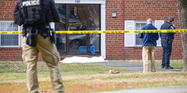 Law enforcement personnel work at the scene which appears to show a body covered under a white blanket outside of an apartment, Wednesday, Feb. 12, 2020, in Baltimore.
