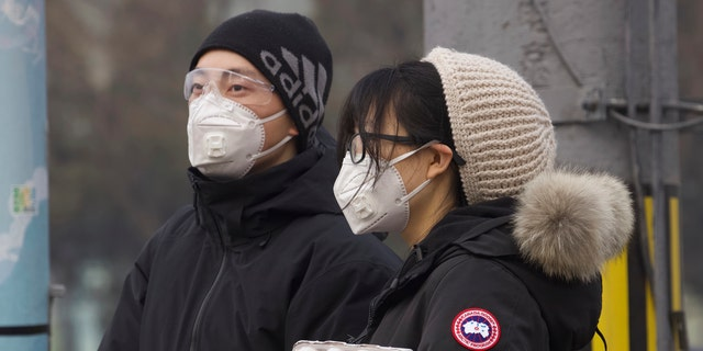 Residents wearing masks wait at a traffic light in Beijing, China Thursday, Feb. 13, 2020. (AP Photo/Ng Han Guan)