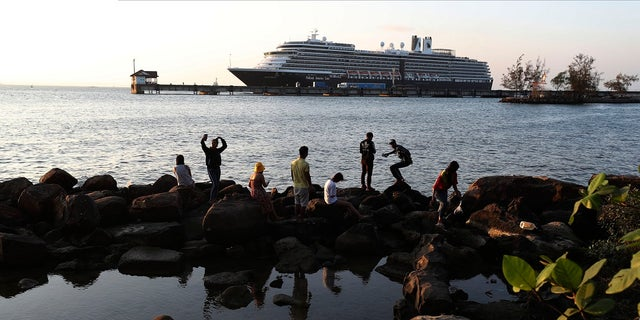 Locals come down to view the Westerdam cruise ship, owned by Holland America Line, docked at the port of Sihanoukville, Cambodia. The Westerdam, turned away by four Asian and Pacific governments due to virus fears, anchored Thursday off Cambodia for health checks on its 2,200 passengers and crew. (AP Photo/Heng Sinith)