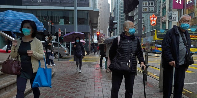 People wearing protective face masks walk on a street in the rain in Hong Kong, Friday, Feb. 14, 2020. COVID-19 viral illness has sickened tens of thousands of people in China since December. (AP Photo/Vincent Yu)