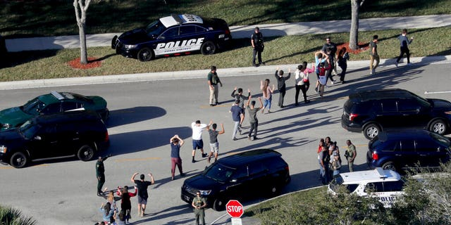 Feb. 14, 2018: Students hold their hands in the air as they are evacuated by police from Marjory Stoneman Douglas High School in Parkland, Fla., after a shooter opened fire on the campus. (Mike Stocker/South Florida Sun-Sentinel via AP, File)