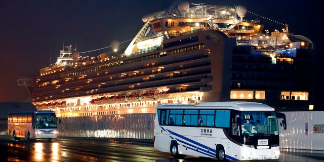 Buses carrying U.S. passengers who were aboard the quarantined cruise ship the Diamond Princess, seen in the background. (Jun Hirata/Kyodo News via AP)