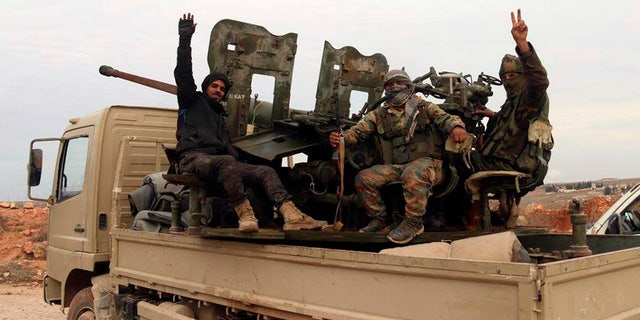 In this photo released Sunday, Feb. 16, 2020 by the Syrian official news agency SANA, Syrian army soldiers flash the victory sign as they patrol the village of Tallet Shweihna, in Aleppo province, Syria. (SANA via AP)