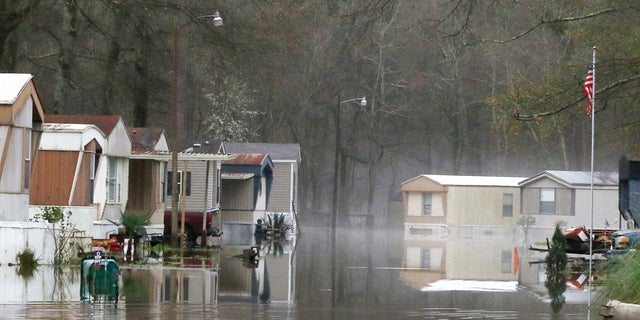 Standing floodwater from the Pearl River still surrounds a number of mobile homes in the back portion of the Harbor Pines community in Ridgeland, Miss., Tuesday, Feb. 18, 2020. (AP Photo/Rogelio V. Solis)