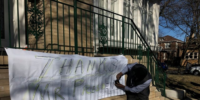 """Ziff Sistrunk of Chicago places a sign of support in front of the home of Patti Blagojevich, wife of former Illinois Gov. Rod Blagojevich, in the Ravenswood neighborhood of Chicago on Tuesday, Feb. President Donald Trump commuted the 14-year prison sentence of Blagojevich Tuesday, calling the sentence """"ridiculous."""" (AP Photo/Charles Rex Arbogast)"""