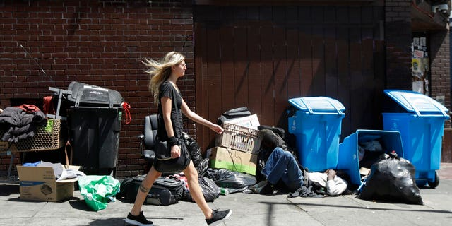 A woman walks past a homeless man sleeping in front of recycling bins and garbage on a street corner in San Francisco.
