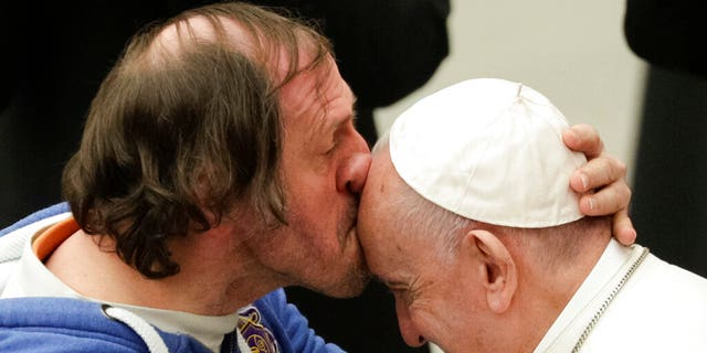 Pope Francis is kissed by a man during his weekly general audience, at the Pope Paul VI hall, at the Vatican, Wednesday, Feb. 19, 2020.