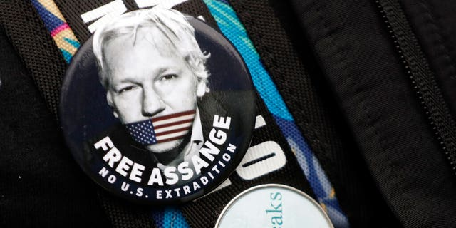 Badges worn by a demonstrator outside Westminster Magistrates Court in London, Wednesday, Feb. 19, 2020.