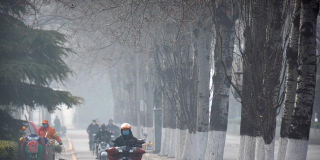 People wear face masks as they ride along a road in Beijing, Friday, Feb. 21, 2020. (Associated Press)