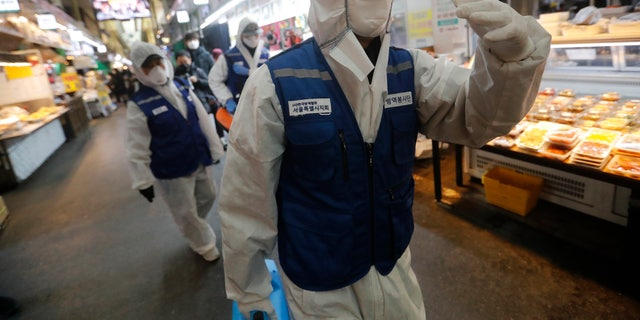 "Workers wearing protective gears arrive to spray disinfectant as a precaution against the coronavirus at a market in Seoul, South Korea, Monday, Feb. 24, 2020. South Korean President Moon Jae-in said his government had increased its anti-virus alert level by one notch to ""Red,"" the highest level. It allows for the temporary closure of schools and reduced operation of public transportation and flights to and from South Korea. (AP Photo/Ahn Young-joon)"