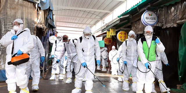 "Workers wearing protective suits spray disinfectant as a precaution against the coronavirus at a market in Bupyeong, South Korea, on Monday. South Korea reported another large jump in new virus cases Monday a day after the president called for ""unprecedented, powerful"" steps to combat the outbreak that is increasingly confounding attempts to stop the spread. (Lee Jong-chul/Newsis via AP)"